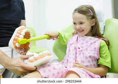 Smiling little girl in dentists chair, being educated about proper tooth-brushing by her paediatric dentist. Early prevention, raising awareness, oral hygiene demonstration concept.