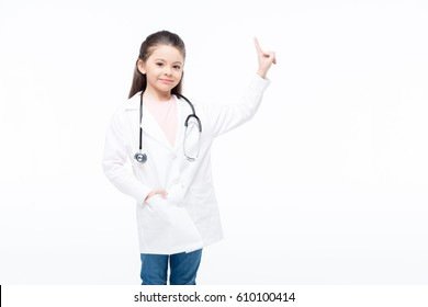 Smiling little girl in doctor costume pointing up with finger  isolated on white
