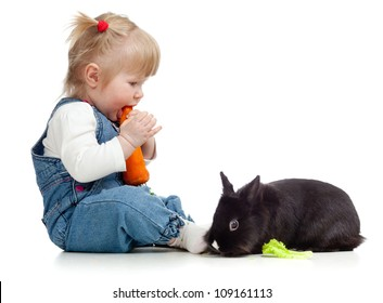 Smiling little girl eating a carrot and feeding rabbit