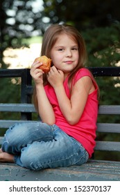 Smiling little girl eats patty in the summer park