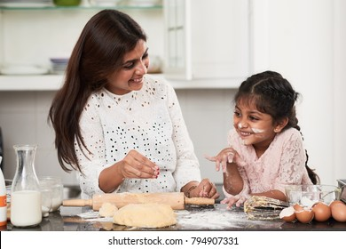 Smiling little girl with face smeared with flour looking away while helping her pretty middle-aged mother to make dough for delicious cupcakes