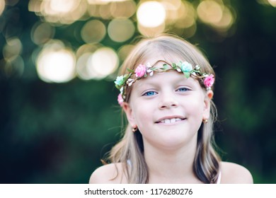 smiling little girl with a floral wreath on her head