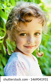 smiling little girl with green leaves outdoors