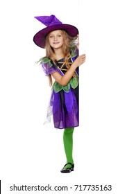 Smiling little girl in halloween witch fancy dress holding the blank board isolated on white