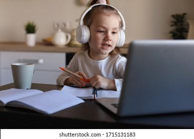 Lächelnd kleine Mädchen in Kopfhörern Handschrift-Studie online mit Laptop zu Hause, süße kleine Kind in Kopfhörern nehmen Internet-Unterricht oder Klasse auf PC.