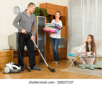 Smiling little girl helping happy parents to clean at living room. Focus on man