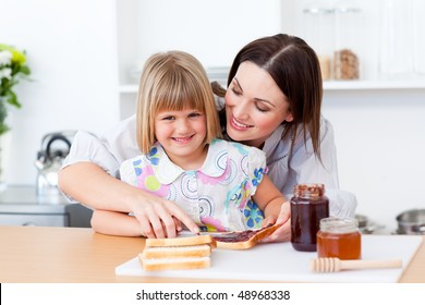 Smiling little girl and her mother preparing toasts in the kitchen