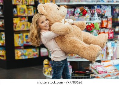 Smiling little girl holding big teddy bear while standing at the supermarket