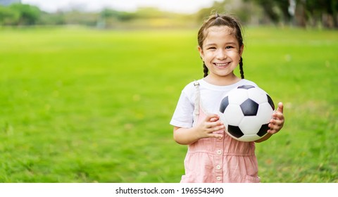Smiling little girl holding soccer ball standing at green football field in summer day. Portrait of little girl athlete playing with a ball at stadium. Active childhood concept. Copy space