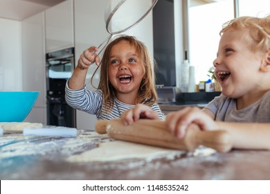 Smiling little girl holding a strainer with boy making dough using rolling pin on kitchen table. Kids having fun while making cookies in kitchen.