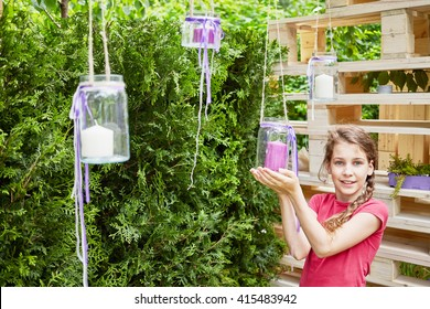 Smiling little girl holds in hands hanging glass jar with candle inside in alcove at park.