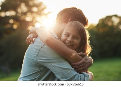Smiling little girl hugging her father outside