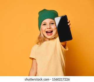 Smiling little girl kid in green modern winter hat showing blank screen of new popular mobile phone on light yellow background