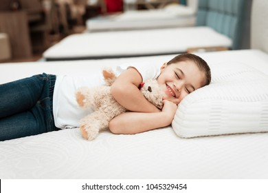 Smiling little girl lies on n orthopedic mattress in a furniture store. Smiling little girl hugs teddy bear on mattress in furniture store.