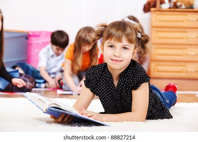 Smiling little girl lies on the floor with a book
