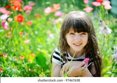 Smiling little girl with long dark hair sitting on poppy field