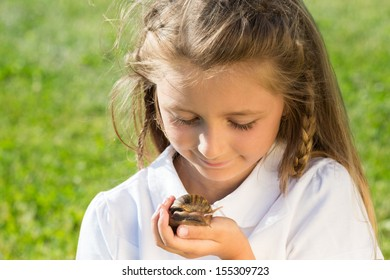 Smiling little girl looking on a large snail in hand