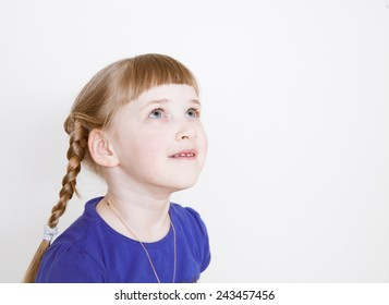 Smiling little girl looking up, white background