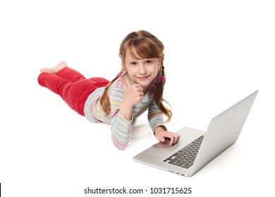 Smiling little girl lying on stomach on the floor with laptop, gesturing thumb up, over white background