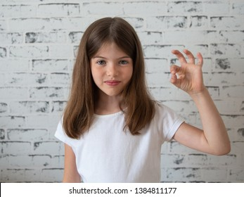smiling little girl model in blank white t-shirt showing ok gesture