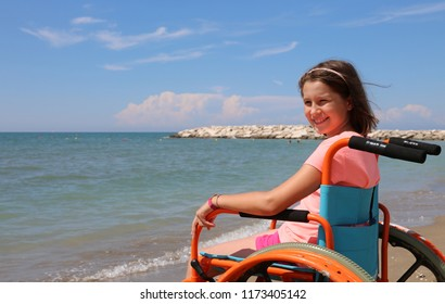 smiling little girl on the wheelchair on summer by the sea
