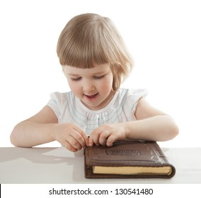 Smiling little girl opening a book; isolated on white