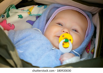 Smiling little girl with a pacifier in his mouth in his wheelchair