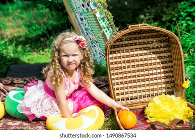 Smiling little girl with picnic basket sitting in meadow in a tent