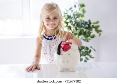 A smiling little girl with piggy bank and money at home