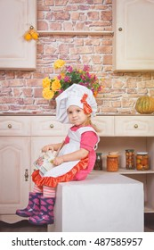 Smiling little girl in pink dress and white apron in the kitchen
