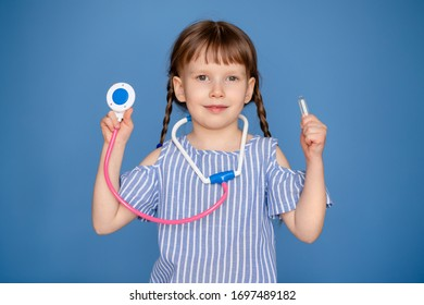 Smiling little girl playing a doctor and listening to a teddy bear with a stethoscope isolated on a blue background. Veterinary clinic game. The concept of the future profession.