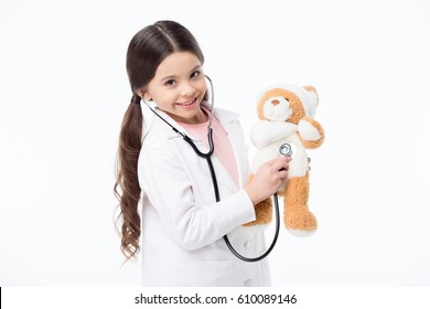 Smiling little girl playing doctor and listening teddy bear with stethoscope isolated on white