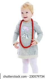 smiling little girl put on her red beads on a white background