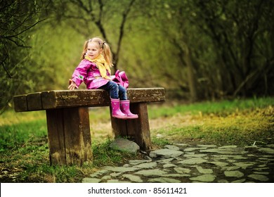 smiling little girl in raincoat and boots outdoor