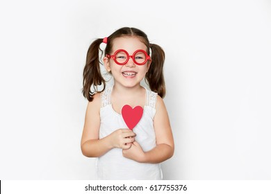 smiling little girl in red toy glasses