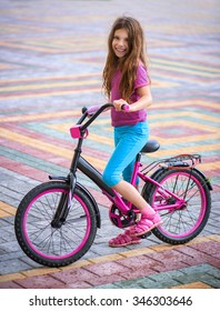 Smiling little girl riding bicycle in city park.