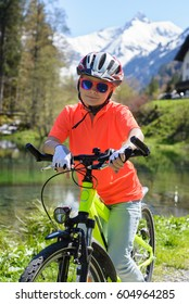 Smiling little girl riding a bike in a beautiful mountain landscape