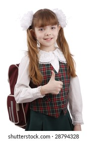 Smiling little girl in school uniform. Young pupil is going to school. School girl showing thumbs up on white background.  School girl is giving an ok gesture with her forward hand. Girl shows OK.