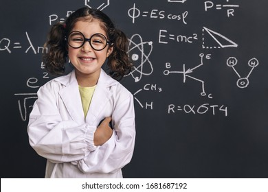 smiling little girl science student with glasses in lab coat on school blackboard background with hand drawings science formula pattern, back to school and successful female career concept