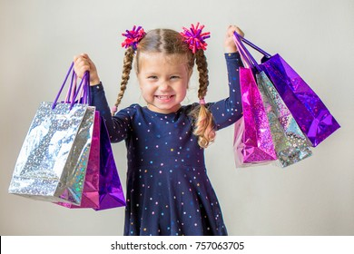 Smiling little girl with shopping bags with gifts. Happy child holds a lot of shopping bags with gifts. Black Friday, sale, holidays concept. Kids shopping