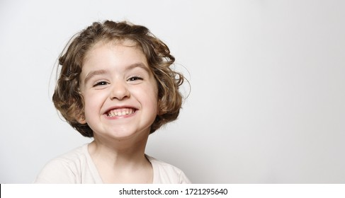 Smiling little girl with short hair and light clothes isolated on light background
