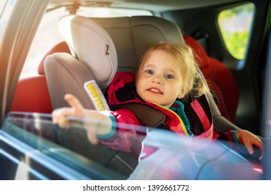 smiling little girl sitting in a child car seat