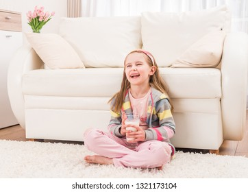Smiling little girl sitting in front of a couch with glass of milk