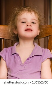 Smiling little girl sitting on a chair closeup