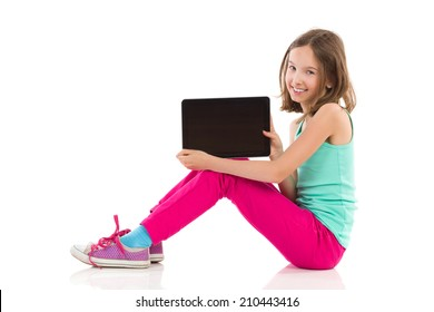 Smiling little girl sitting on the floor and showing a digital tablet. Full length studio shot isolated on white.
