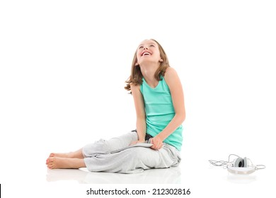 Smiling little girl sitting on the floor with digital tablet and headphones and looking up. Full length studio shot isolated on white.