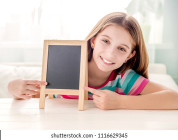 Smiling little girl sitting at a table with empty small chalkboard