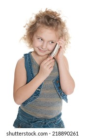 A smiling little girl speaks on a cell phone against the white background