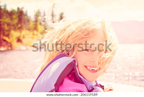 Smiling Little Girl in a Speedboat in the Summer Sun