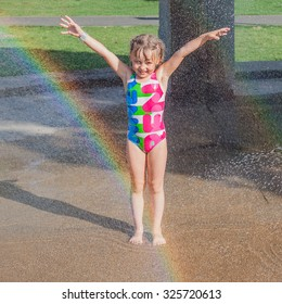 Smiling little girl standing in streams of city splash pad fountains. Kid happy to be wet and fresh. Rainbow in the fountain.